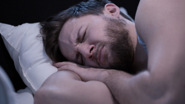Portrait of young sleeping man having nightmares